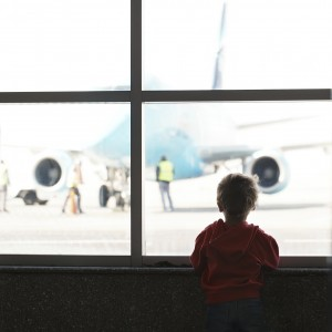Boy looks at the plane at the airport silhouette shot from back